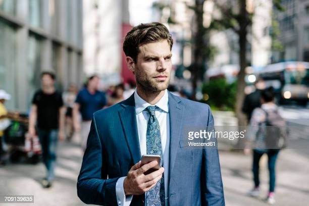 Handsome businessman walking in Manhattan, using mobile phone
