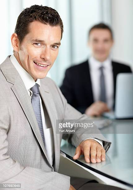 handsome businessman with colleague in background - number of people stock photos and pictures