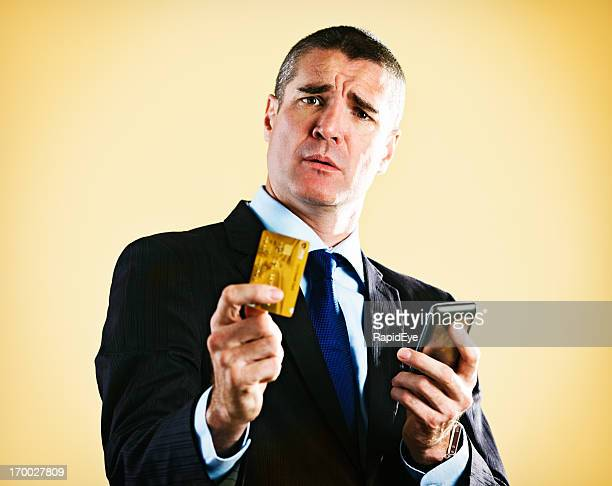 Handsome businessman with credit card and phone seems worried
