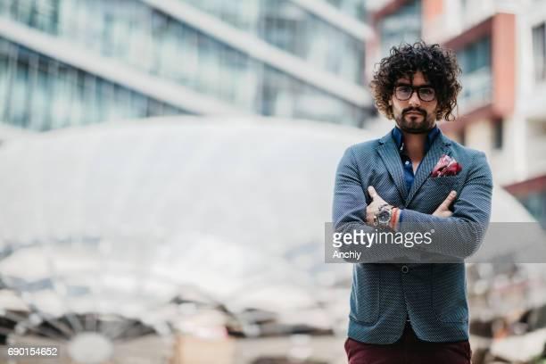 Gut aussehend Geschäftsmann mit lockigem Haar Stand mit verschränkten Armen