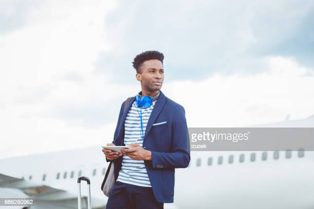 Handsome businessman with digital tablet in front of airplane