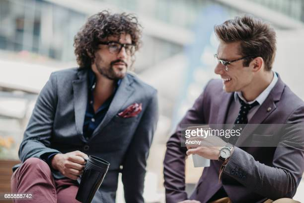 Gut aussehend Geschäftsleute sitzen auf der Bank Chit-Chat während der Kaffeepause