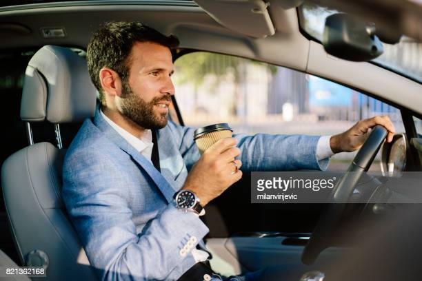 Handsome busnessman driving a car and drinking coffee to go