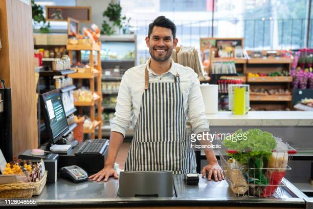 handsome cashier at a supermarket facing camera smiling at the supermarket - cashier stock pictures, royalty-free photos & images