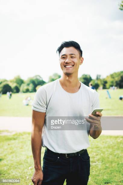 handsome chinese guy with smartphone in park - handsome chinese men stock pictures, royalty-free photos & images