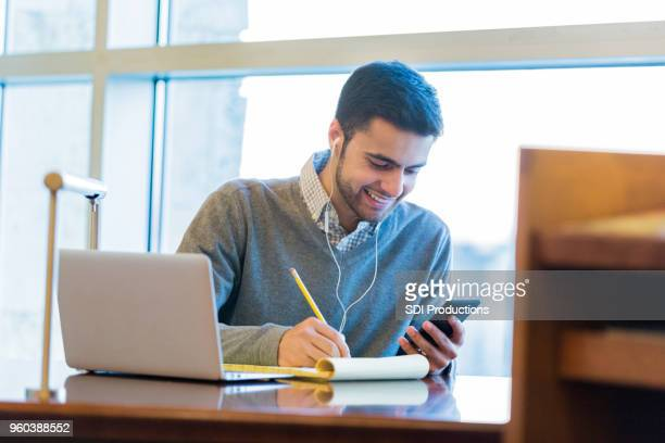 Handsome college student uses technology while studying