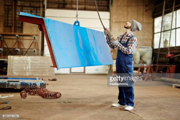 Stilig byggnadsarbetare lyft metalldel