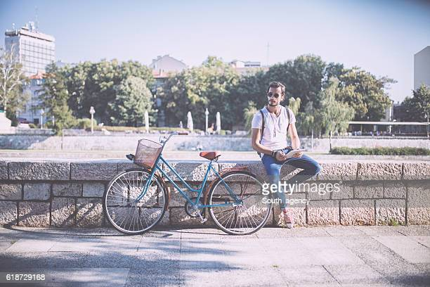 Handsome Cyclist posing outdoors,holding tablet