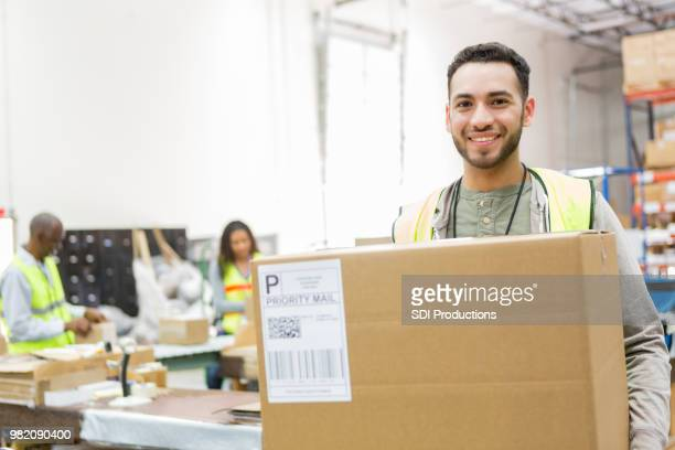 Handsome distribution warehouse employee with prepared package