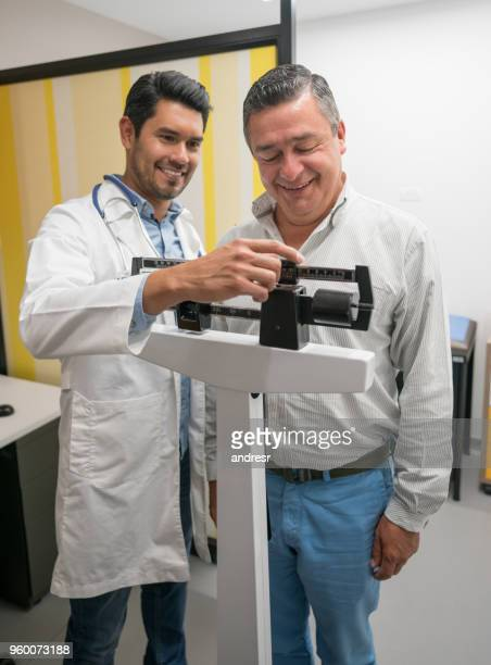 handsome doctor checking the weight of a mid adult male patient both smiling - mass unit of measurement stock pictures, royalty-free photos & images