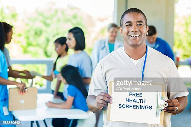 "Handsome doctor holding a """"Free Health Screenings"""" sign"