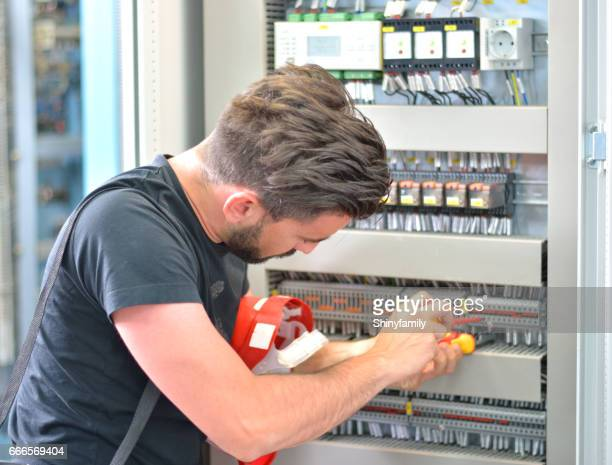 handsome electrician working with work tool in electrical room - fuse stock photos and pictures