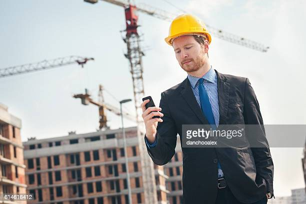 Handsome engineer at construction site using smart phone