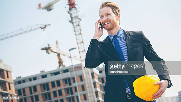 Handsome engineer talking on the mobile phone at construction si