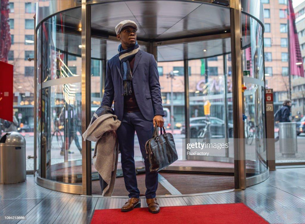 Handsome entrepreneur entering the mall through a revolving door : Stock Photo