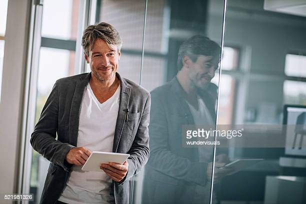 Handsome european business executive leaning against office window holding tablet.