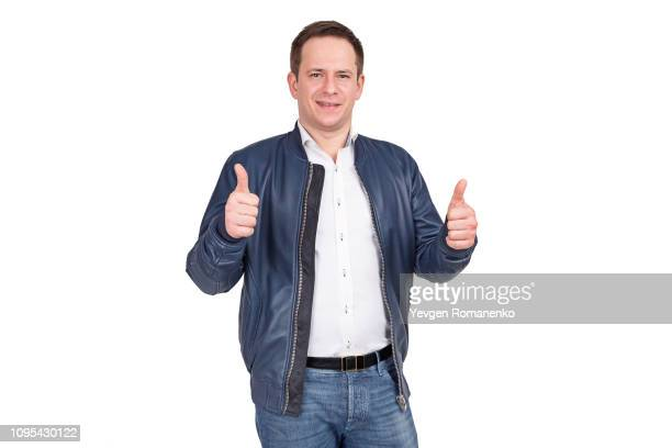handsome european man in white shirt, blue jeans and blue leather jacket holds his thumbs up. isolated on white background. - leather jacket stock pictures, royalty-free photos & images