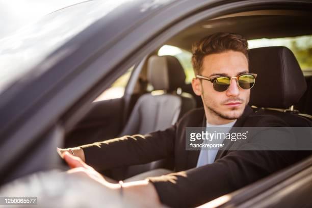 handsome fashion man driving - só homens jovens imagens e fotografias de stock
