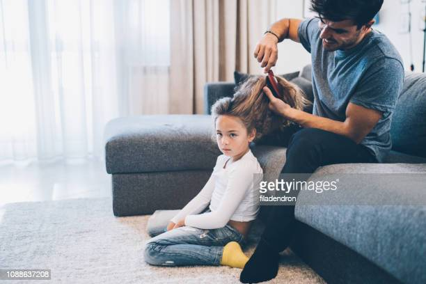 Handsome father brushing hair of daughter