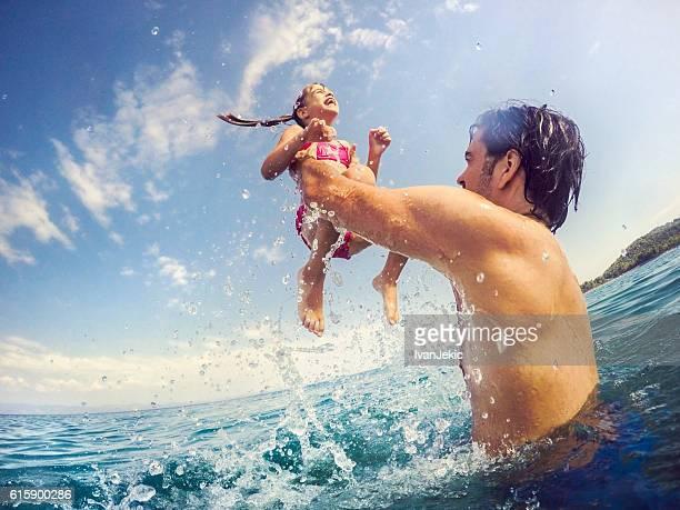 handsome father jumping with his daughter in sea - strandurlaub stock-fotos und bilder