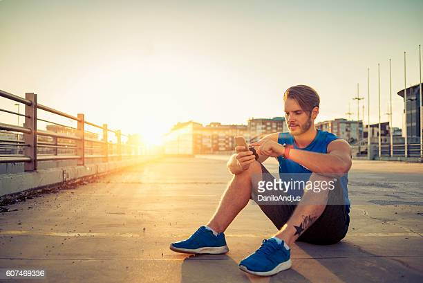 handsome fit man using his smartphone after workout