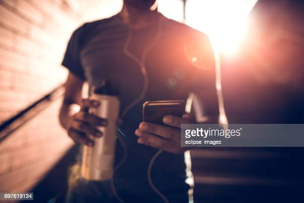 Bel homme apte à l'aide de son smartphone après entraînement
