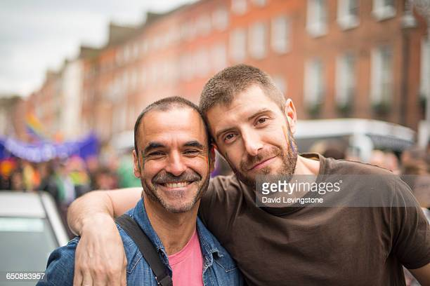 handsome gay couple during gay pride parade - lesbienne photos et images de collection