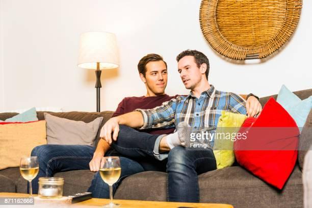 Schöne Homosexuell Paar zusammen vor dem Fernseher zu Hause in ihrem Wohnzimmer