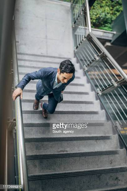 handsome gentleman walking up the steps downtown in taipei - south_agency stock pictures, royalty-free photos & images