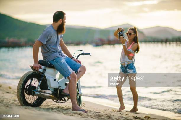 A handsome girl shooting photos of her lumbersexual boyfriend, he leaned on an oldie motorbike, posing. They are having fun at the beach watching sunset