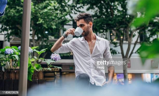 handsome guy having coffee - top bianco foto e immagini stock