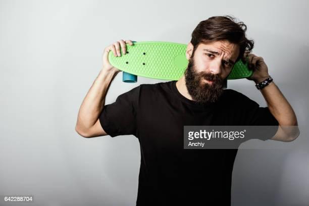 Handsome guy holding penny skateboard on his shoulders