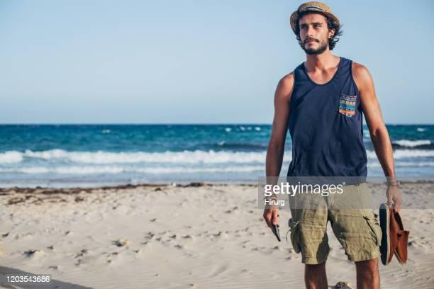 bel ragazzo con cappello è sulla spiaggia - canotta foto e immagini stock