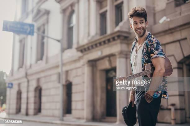 hübscher kerl mit ukulele - gitarre stock-fotos und bilder