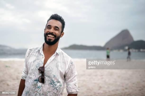 handsome happy bearded young brazilian man at beach in Rio de Janeiro