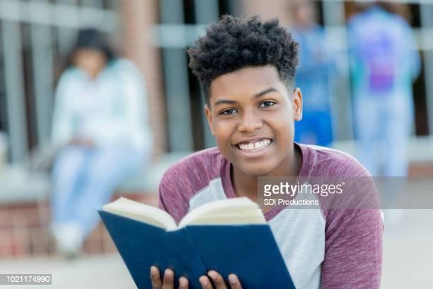 handsome high school boy reads book on campus - olhos castanhos imagens e fotografias de stock