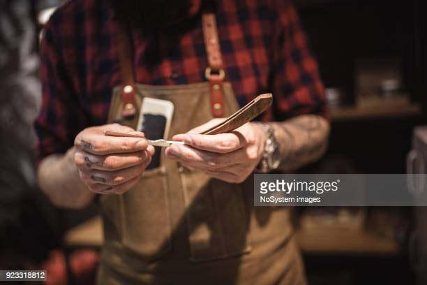 handsome, hipster barber at his barber shop, holding razor. close up, no face shot - razor stock photos and pictures