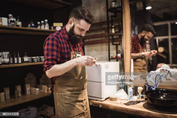 handsome, hipster barber at his barber shop, working - razor stock photos and pictures