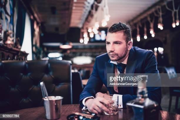 Hipster bel homme d'affaires Golding verre de Whisky et de fumer dans un Bar