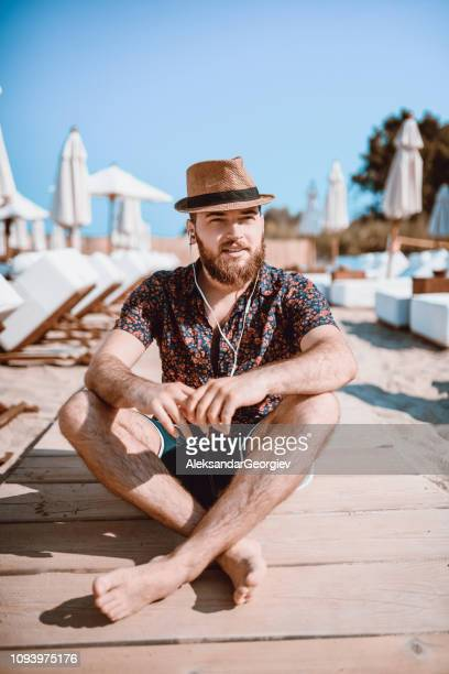 Handsome Hipster Enjoy The Empty Beach In Meditating Position
