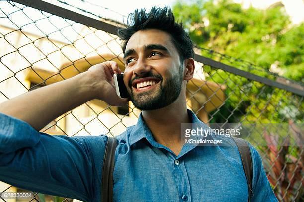 Handsome Indian man talking using mobile phone.