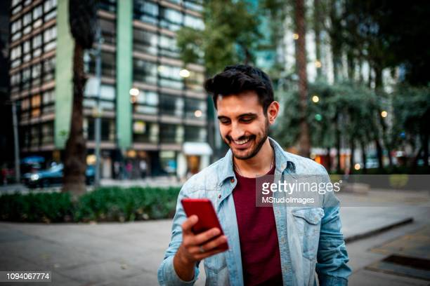handsome indian man using mobile phone. - indian ethnicity stock pictures, royalty-free photos & images