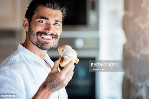 handsome italian having his croissant - french food stock pictures, royalty-free photos & images
