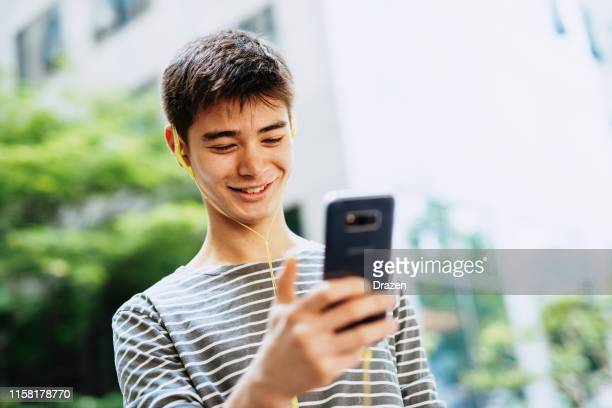 handsome korean man using mobile phone outdoors - east asian ethnicity stock pictures, royalty-free photos & images