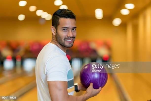 笑みを浮かべてカメラを見てボウリングのボールを投げる準備ができてハンサムなラテン アメリカ人 - ボーリング場 ストックフォトと画像