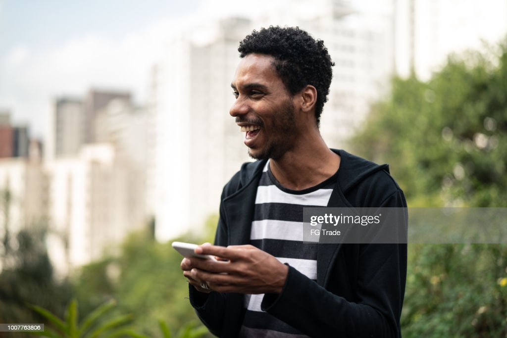 Handsome latino african man using mobile : Stock Photo