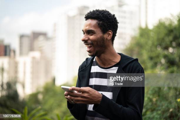 handsome latino african man using mobile - brazilian men stock photos and pictures