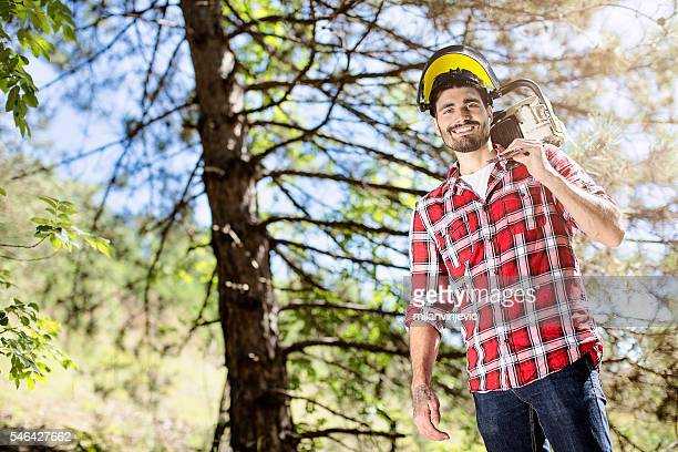 Handsome lumberjack posing with chainsaw in forest