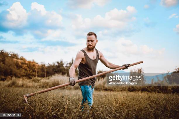 Handsome Male Agricultural Worker Mowing The Dry Lawn
