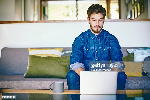 Handsome male blogger using laptop at coffee table